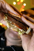 Young man eating a burger. - Paul Box - 28-11-2004
