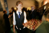 A waitress serving strawberies covered in chocolate at a party or reception. - Paul Box - 28-11-2004