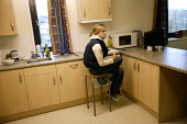 A student sits in her communal kitchen. The University of Bath. - Paul Box - 2000s,2004,accommodation,COOKERY,cooking,EDU Education,facilities,halls,Higher Education,housing,kitchen,KITCHENS,modern,of,residence,room,rooms,shared,student,students,university