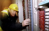 Electricians working onsite. - Paul Box - 2000s,2004,BUILDER,builders,building site,Construction Industry,dangerous,electric,electrical,Electrician,Electricians,hard hat,hat,hats,hazard,hazardous,hazards,HEA Health & safety,industrial,jackets