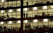 Office workers talking in their office, silhouetted in window - Paul Box - 01-11-2004