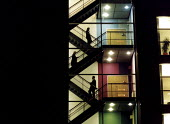 Business workers walking up the stairs , silhouetted in window. - Paul Box - 01-11-2004