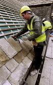 Roofer lays slates on roof of barn renovation on building site. - Paul Box - 01-11-2004