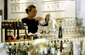 A waitress with wine glasses in trendy bar - Paul Box - 01-11-2004
