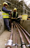 Plumbers install an industrial size water supply on building site. - Paul Box - 2000s,2004,BUILDER,builders,building,building site,BUILDINGS,construction,Construction Industry,copper,cutting,EBF Economy,fitter,fitters,hard hat,hat,hats,jackets,job,jobs,joining,joint,LAB LBR work,