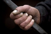 Workers at a Scrap yard in North wales. An oily hand grabs a metal bar - Paul Box - 20-03-2005