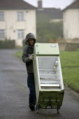 A resident removes an old fridge. Council Houses in Filton, Bristol. They were built in the 1950s and are suffering from concrete decay due to Alkali Silica reaction. They are being demolished and the... - Paul Box - 24-03-2005