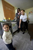 A family with children. A resident outside condemmed home. Council Houses in Filton, Bristol. They were built in the 1950s and are suffering from concrete decay due to Alkali Silica reaction. They are... - Paul Box - 1950's,2000s,2005,a,accommodation,adult,adults,affordable,babies,baby,bad,black,BME Black minority ethnic,cheap,child,CHILDHOOD,children,cities,City,communities,community,concrete,condemed,cost,Counci