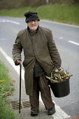 An elderly disabled man searchs for fuel for his fire from the roadside, in an area of rural poverty in south west Wales - Paul Box - 20-04-2005