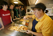 A dinner lady serves burger and chips to pupils at a secondary school in the west country. - Paul Box - 10-04-2005