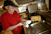 A dinner lady frying chips at a secondary school in the west country. - Paul Box - 10-04-2005