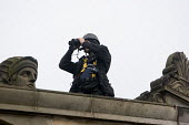 Anti war march, Edinburgh. A police officer with binoculars on a roof keeps an eye on the demonstraters. - Paul Box - 2000s,2005,activist,activists,adult,adults,against,anti,anti capitalism,BINOCULAR,binoculars,CAMPAIGN,campaigner,campaigners,CAMPAIGNING,CAMPAIGNS,capitalism,capitalist,clj,DEMONSTRATING,demonstration