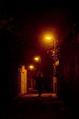 A woman walks through the streets at night down an alley way. - Paul Box - 07-12-2005