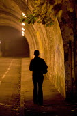 A woman walks through the streets at night down an underpass. - Paul Box - 07-12-2005