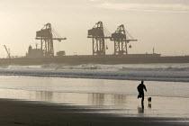 Runner on the beach in Port Talbot, Wales. - Paul Box - 2000s,2005,aberavon,and,animal,animals,beach,BEACHES,canine,capitalism,capitalist,coast,coastal,coasts,corus,country,countryside,crane,cranes,degradation,dock,docks,dog,dogs,EBF Economy,eni,eni enviro