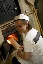 A baker stokes the bread oven , Hobbs house bakery, nr Bristol. - Paul Box - 05-12-2005