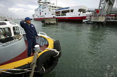 A crew member from a tug boat in Cowes .The Red Funnel passenger ferry is in the background. - Paul Box - 05-12-2005