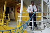 A crew member ties up the Red Funnel ferry after arriving in Cowes. - Paul Box - 2000s,2005,ARRIVAL,arrivals,arrive,arrived,arrives,arriving,boat,boats,capitalism,capitalist,channel,cowes,crew,crewman,crewmen,crewmenmaritime,EBF Economy,Ferries,Ferry,Funnel,Industries,industry,Isl