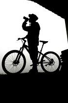 Mountain bikers seek shelter and rehydrate. - Paul Box - 2000s,2005,bike,bikers,bikes,biking,Biking Trail,bottle,BOTTLES,cyclists,dehydrated,DEHYDRATION,drink,drinking,event,fluid,helmets,hobbies,hobby,hobbyist,LFL leisure,mountain,mountain biking,MOUNTAINS