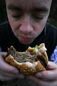 A man eats a half pound burger. - Paul Box - 2000s,2005,bad,beef,beef burger,beef burgers,beefburger,BEEFBURGERS,bun,burger,burgers,chew,chewing,cholestrol,Convenience,diet,diets,eat,eating,fast,fast food,fast food,fastfood,fatty,food,FOODS,hamb