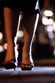 A woman walks home at night after a night out on the town. - Paul Box - 2000s,2005,after,at,at night,cities,City,dangerous situation,dark,female,going out,hand bag,heels,high heels,home,light,lighting,lights,lone alone,lonely woman,night,night out,night out the town,night