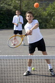 Hanham high school, Bristol. School pupils playing tennis. - Paul Box - 2000s,2005,activity,ball,boy,boys,child,CHILDHOOD,children,cities,city,class,comprehensive,COMPREHENSIVES,court,EDU Education,education,exercise,exercises,exercising,fit,fitness,game,games,getting,juv