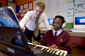 Hanham high school, Bristol. A music teacher helping a student on a keyboard. - Paul Box - 06-12-2005