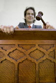 An auctioneer stands on the lectern at an auction house. - Paul Box - 2000s,2005,auction,auctioneer,auctioneers,AUCTIONS,bid,bidding,EBF Economy,gavel,hammer,job,jobs,LAB LBR work,mallet,people,public,sale,the,under,worker,workers,working