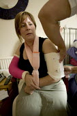 An outpatient is treated by a district nurse at her home. - Paul Box - 2000s,2005,a,accident,accidental,ACCIDENTS,arm,arms,bandage,bandaging,broken,changing,community nurse,district,dressing,FEMALE,HEA Health,home helps,hospital,HOSPITALS,hygiene,job,jobs,key,LAB LBR wor