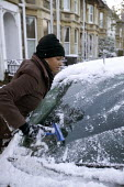 Snow is scraped off a car , Bristol - Paul Box - 2000s,2005,BAME,BAMEs,black,BME,BME Black minority ethnic,bmes,clearing,cold,conditions,dangerous,diversity,DRIVER,DRIVERS,driving,ethnicity,FEMALE,frost,landscape,LANDSCAPES,minorities,minority,outdo