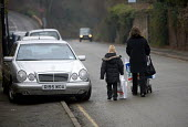 A motorist parks on pavement causing an obstruction to pedestrians. - Paul Box - 2000s,2006,adult,adults,and,AUTO,AUTOMOBILE,AUTOMOBILES,AUTOMOTIVE,bad,blocked,car,cars,cross,crosses,crossing,curb,FAMILY,FEMALE,highway,inconsiderate,MATURE,mother,MOTHERHOOD,MOTHERING,MOTHERS,motor
