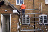 An new housing estate of social housing provision is built in Wiltshire. A brick layer at work. - Paul Box - 2000s,2006,blocks,BRICK,bricklayer,bricklayers,bricklaying,bricks,build,builder,builders,building,building site,BUILDINGS,cold,construction,Construction Industry,EBF Economy,hard hat,hat,hats,house,ho