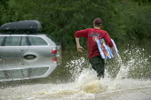 A boy goes surfing in flood water after the river Avon burst its banks, Welford On Avon, near Stratford upon avon, Warwickshire. - Paul Box - 21-07-2007