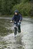 A cyclist rides down a flooded road after the river Avon burst its banks, Welford On Avon, near Stratford upon avon, Warwickshire. - Paul Box - 22-07-2007
