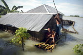 A group of people are caught in the flooding in Manikgonj, 50 kilometers (31 miles) north of Dhaka, Saturday, Aug. 7, 2007. At least 1.8 million were driven from their homes by monsoon rains across no... - Palash khan - 2000s,2007,asian,asians,BAD,bangladesh,Bangladeshi,Bangladeshis,boat,boats,child,CHILDHOOD,children,Climate Change,dia disaster disasters,eni environmental issues,EXTREME,families,family,FEMALE,flood,