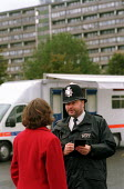 Police officer talking to a resident. Mobile police station opposite the Aylesbury housing Estate, Southwark, South London. - Philip Wolmuth - 14-10-2002
