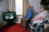 Mr and Mrs Ravenscroft-Reid, watch television in their flat in a sheltered housing scheme in Stevenage to which they transferred from their former home in Haringey, North London. - Philip Wolmuth - 01-02-2001