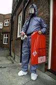 A local authority Environmental Health Officer wearing protective clothing carries asbestos waste from a building in Haringey, North London. - Philip Wolmuth - 15-07-1993