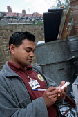 Bethnal Green Neighbourhood Warden Doraj Miiah makes a report on illegally dumped rubbish in a Tower Hamlets back street - Philip Wolmuth - 19-05-2003