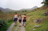 Three teenagers walk on a public footpath leading to the summit of Cnicht, above the village of Croesor in the Snowdonia National Park, Wales. - Philip Wolmuth - 11-08-2003