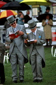 Father and son study the race programme in front of The Queen's Stand at Epsom Downs on Derby Day - Philip Wolmuth - 2000s,2001,adolescence,adolescent,adolescents,AFFLUENCE,AFFLUENT,bet,BETS,betting,Bourgeoisie,cities,city,class,Derby,Domesticated Ungulates,elite,elitism,EQUALITY,equestrian,equine,families,FAMILY,fl