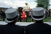 Racegoers watch the horses parade in the Paddock at Epsom Downs racecourse on Derby Day. - Philip Wolmuth - 2000s,2003,a,AFFLUENCE,AFFLUENT,animal,animals,bet,BETS,betting,Bourgeoisie,cities,city,class,Derby,domesticated ungulate,domesticated ungulates,elite,elitism,EQUALITY,equestrian,equine,flat,gambling,
