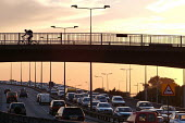 A cyclist crosses a bridge above rush hour traffic as drivers commute to work on the North Circular Road in West London - Philip Wolmuth - 15-09-2003