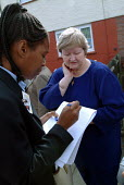 A tenant requests a repair from a Haringey Council housing officer on Coldfall Estate, Tottenham. London - Philip Wolmuth - 2000s,2003,afro-caribbean,BAME,BAMEs,black,BME,bmes,building,BUILDINGS,cities,city,cos,Council,Council Services,Council Services,cultural,diversity,ethnic,ethnicity,FEMALE,group,groups,home,housing,jo