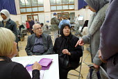 Elderly Iraqi refugees use an interpreter to talk with citizens advice bureau staff and banking advisors at an open day at the Beethoven Centre, Queens Park, London. - Philip Wolmuth - 2000s,2003,adult,adults,Advice,ADVISE,ADVISER,advisers,advising,advisor,ADVISORS,age,ageing population,and,asylum,Asylum Seeker,Asylum Seekers,Asylum Seeker,Asylum Seekers,BAME,BAMEs,bilingual,Black,B
