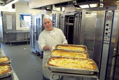 An employee in the kitchen at Homerton Hospital, Hackney, east London, employed by multinational ISS Mediclean. - Philip Wolmuth - 29-02-2004