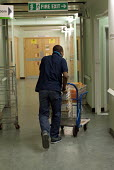 A porter at Homerton Hospital, Hackney, east London, employed by multinational ISS Mediclean in portering services. - Philip Wolmuth - 29-02-2004