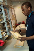A porter in the post room at Homerton Hospital, Hackney, east London - Philip Wolmuth - 29-02-2004
