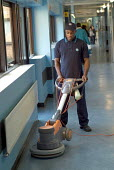 A domestic mops the floor in a ward at Homerton Hospital, Hackney, east London employed by multinational ISS Mediclean in cleaning services. - Philip Wolmuth - 29-02-2004