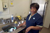 A domestic washes dishes on a ward at Homerton Hospital, Hackney, east London, employed by multinational ISS Mediclean in cleaning services. - Philip Wolmuth - 2000s,2004,BAME,BAMEs,black,BME,bmes,cities,city,clean,cleaner,cleaners,cleaning,cleansing,contract,dishes,diversity,domestic,EARNINGS,EQUALITY,ethnic,ethnicity,FEMALE,Hackney,hea health,Hospital,HOSP
